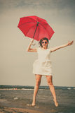 Girl jumping with red umbrella on beach. Royalty Free Stock Image
