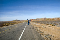 Girl jumping in road. Girl jumping on road in New Mexico Royalty Free Stock Photography