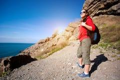 Girl jumping on a rock against the blue sky Stock Photos