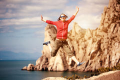 Girl jumping on a rock against the blue sky Stock Photo