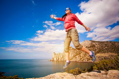 Girl jumping on a rock against the blue sky Stock Image