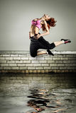 Girl jumping on the roof Stock Images