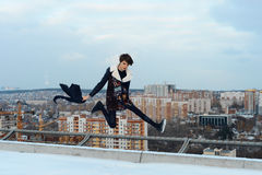 Girl jumping on the roof in the city. Cute girl jumping on the roof in the city Royalty Free Stock Images