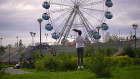 Young woman is jumping rope in the park on the background of the Ferris wheel. slow-motion stock footage