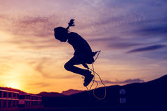 Girl  jumping rope in silhouette with sun set Stock Photos