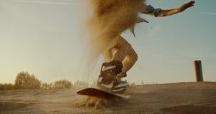 Girl jumping on sandboard in desert at sunset