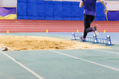Girl jumping into sandpit on long jump competition Stock Photos