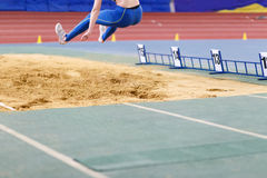 Girl jumping into sandpit on long jump competition Royalty Free Stock Photography