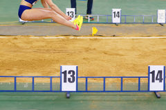 Girl jumping into sandpit on long jump competition Stock Images