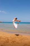 Girl jumping. On a sandy beach Stock Photos