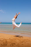 Girl jumping. On a sandy beach royalty free stock photography