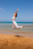 Girl jumping. On a sandy beach royalty free stock image