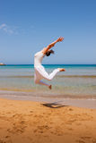 Girl jumping. On a sandy beach royalty free stock photos