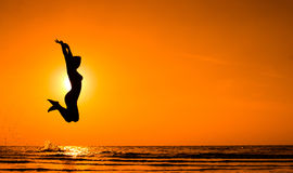 Girl jumping in Sea Sunset Royalty Free Stock Photography
