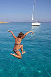 Girl jumping in sea. Young girl jumping into blue sea with yacht in background Royalty Free Stock Photography