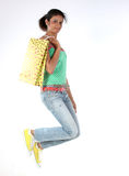 Girl jumping with shopping bags Stock Images