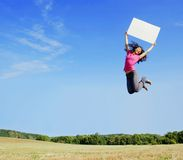 Girl Jumping With Sign. Girl jumping with a blank sign in a field stock photos