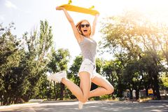 Girl jumping with skateboard. Cheerful young girl jumping with skateboard outdoors Royalty Free Stock Photos