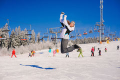 Girl jumping on ski slope. Young woman happily jumping on  background of  ski slope in winter Stock Images