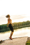 Girl jumping skipping rope on the lake Stock Images