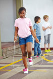 Girl jumping with skipping rope. On schoolyard in elementary school Stock Images