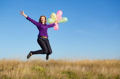 Girl jumping. Smiling girl jumping with balloons Stock Photography