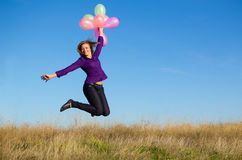 Girl jumping. Smiling girl jumping with balloons Royalty Free Stock Photography