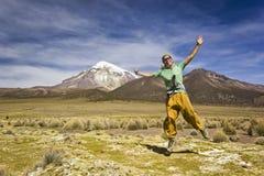 Girl jumping and smiling near volcano Sajama in Bolivia Stock Image