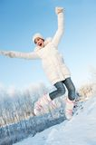 Girl jumping in the snow Stock Photography