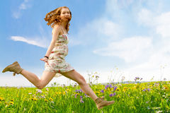 Girl jumping on a spring meadow Stock Photos