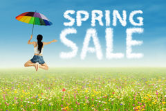 Girl jumping beside spring sale clouds Stock Images