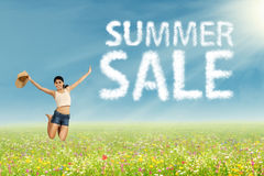 Girl jumping with summer sale sign Stock Photo
