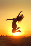 Girl jumping in the sunset Royalty Free Stock Photos