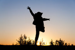 Girl jumping at sunset Stock Images