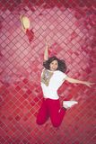 Girl jumping and throwing a hat in front of a red wall. stock images