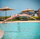 Girl jumping to a swimming pool Stock Images