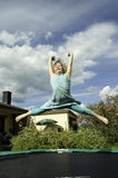 Girl jumping on a trampoline. Stock Photography