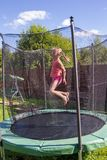 Girl jumping on a trampoline behind protective net. Girl jumping on a trampoline behind a protective net stock photography