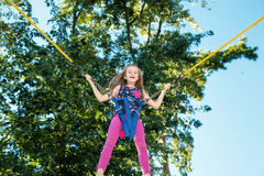 Girl jumping on a trampoline Stock Image