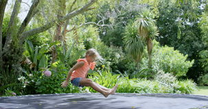 Girl jumping on trampoline stock video footage