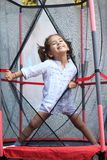 Girl jumping in the trampoline Stock Photography