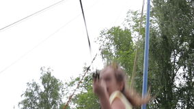 A girl jumping on the trampoline in the summer park stock video footage