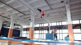 Girl is jumping on trampoline,. Young gymnastic girls is jumping on a trampoline gymnastic hall stock video