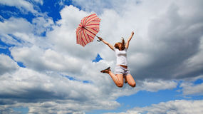 Girl jumping with an umbrella Stock Images