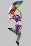 Girl jumping with umbrella. Young and beautiful female jumping high with umbrella over grey background Royalty Free Stock Photography