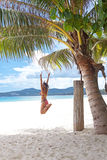 Girl jumping under palm tree Stock Images