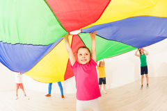 Girl jumping under tent during parachute games. Portrait of smiling little girl jumping under colorful tent during parachute games at sports hall royalty free stock image