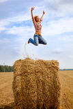 Girl jumping up on straw roll Stock Images