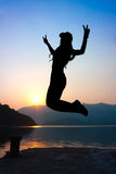 Girl jumping with V sign Royalty Free Stock Image