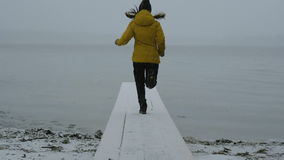 Girl jumping and waving on the shore of the lake on the bridge. Happy winter and snow. 96fps stock footage